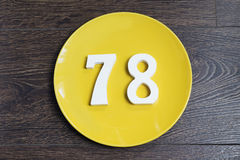 The number seventy-eight on the yellow plate. Figure seventy-eight at the plate yellow and brown background Royalty Free Stock Photo
