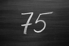 Number seventy five enumeration written with a chalk on the blackboard Stock Photography