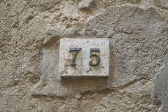 Number seventy five on a wall. With copy space Stock Image