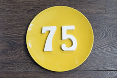 The number seventy-five on the yellow plate. The number seventy-five on the yellow plate and brown background Stock Photo