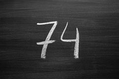 Number seventy four enumeration written with a chalk on the blackboard Royalty Free Stock Photo