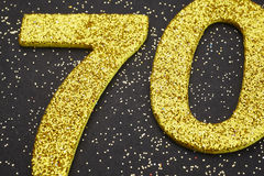 Number seventy golden color over a black background. Anniversary Royalty Free Stock Image