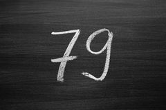 Number seventy nine enumeration written with a chalk on the blackboard Royalty Free Stock Photo