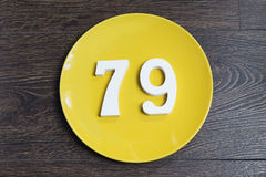 The number seventy-nine on the yellow plate. The number seventy-nine on the yellow plate and brown background Royalty Free Stock Photo