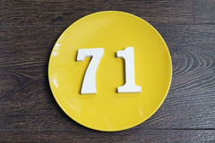 The number seventy-one on the yellow plate. The number seventy-one on the yellow plate and brown background Stock Photography