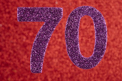 Number seventy purple color over a red background. Anniversary. Horizontal Royalty Free Stock Images