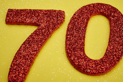 Number seventy red color over a yellow background. Anniversary Stock Photos