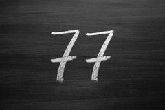 Number seventy seven enumeration written with a chalk on the blackboard Stock Image