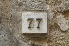 Number seventy seven on a wall. With copy space Royalty Free Stock Image