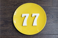 The number seventy-seven on the yellow plate. The number seventy-seven on the yellow plate and brown background Royalty Free Stock Photos