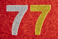 Number seventy-seven yellow silver color over a red background. Anniversary. Birthday Stock Images