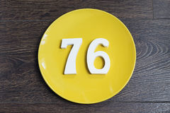 The number seventy-six on the yellow plate. The number seventy-six on the plate yellow and brown background Stock Photos