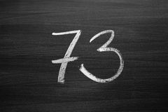 Number seventy three enumeration written with a chalk on the blackboard Stock Photography
