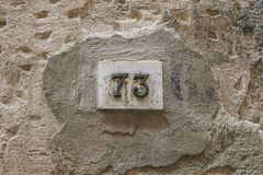 Number seventy three on a wall. With copy space Stock Photography