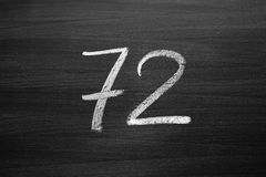 Number seventy two enumeration written with a chalk on the blackboard Stock Photography