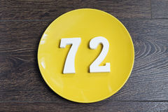 The number seventy-two on the yellow plate. The number seventy-two on the yellow plate and brown background Royalty Free Stock Photo
