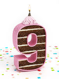 Number 9 shaped chocolate birthday cake with lit candle Royalty Free Stock Images