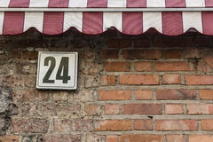 Number 24. Sign #24 on a brick wall, covered by a sunblind stock images