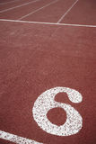 Number six signpost in an athletic running track Stock Photos