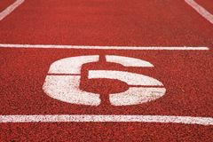 Number six. White athletic track number on red rubber racetrack, texture of racetracks in stadium Stock Photos