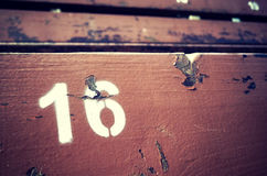 Number sixteen painted on an old wooden seat. Stock Photos