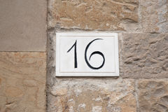 Number Sixteen. On Plaque on Stone Wall Royalty Free Stock Photos