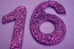 Number sixteen purple color over a purple background. Anniversar Royalty Free Stock Image