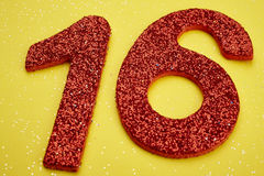 Number sixteen red color over a yellow background. Anniversary Royalty Free Stock Photo