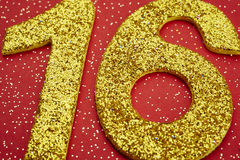 Number sixteen yellow color over a red background. Anniversary Stock Images