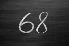 Number sixty eight enumeration written with a chalk on the blackboard Stock Photography