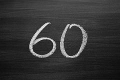 Number sixty enumeration written with a chalk on the blackboard. Closeup view Stock Images