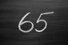 Number sixty five enumeration written with a chalk on the blackboard Royalty Free Stock Photo