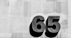 Number sixty-five on wall Stock Image