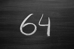Number sixty four enumeration written with a chalk on the blackboard. Closeup view Stock Photo