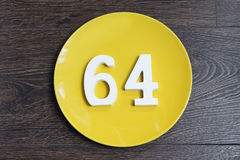 The number sixty-four on the yellow plate. Royalty Free Stock Image