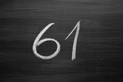 Number sixty one enumeration written with a chalk on the blackboard Stock Photography