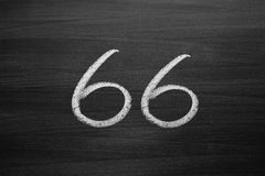 Number sixty six enumeration written with a chalk on the blackboard Stock Image