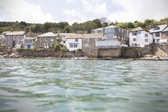 Cottages overlooking Mousehole Harbour in summer. A number of small cottages overlooking the fishing harbour of Mousehole, in Cornwall. Photo taken on a sunny Stock Photography
