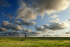 Grassy Hills under Dramatic Sky. A number of street lights set in a row on a grassy hill at a park, beneasth the dramatic cloudy afternoon sky Stock Photos