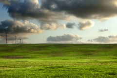 Grassy Hills under Dramatic Sky. A number of street lights set in a row on a grassy hill at a park, beneath the dramatic cloudy afternoon sky Stock Images