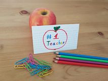 Number 1 Teacher Card With Colored Pencils, Apple And Paper Clips stock photography