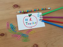 Number 1 Teacher Card With Colored Pencils And Paper Clips stock image