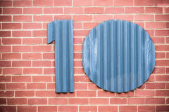 Number Ten. The number ten cut out of corrugated iron and placed on a face brick wall Stock Images