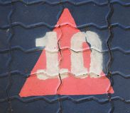 The number ten in a triangle is on the footpath playground. This is the number ten what has painted on bricks Royalty Free Stock Image