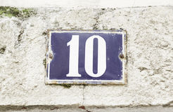 Number ten on a wall. Detail of a number of information on the wall of a house Royalty Free Stock Photo