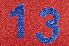 Number thirteen blue color over a red background. Anniversary. Royalty Free Stock Photos