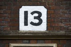 Number thirteen hand painted on plaster background Stock Photo