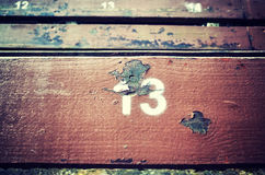 Number thirteen painted on an old wooden seat. Stock Photo