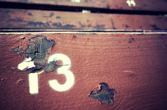 Number thirteen painted on an old wooden seat. Royalty Free Stock Photos