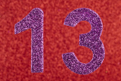 Number thirteen purple color over a red background. Anniversary. Stock Image